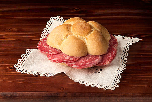 Classic Italian sandwich with salami Classic Italian sandwich with salami on wooden table round loaf stock pictures, royalty-free photos & images
