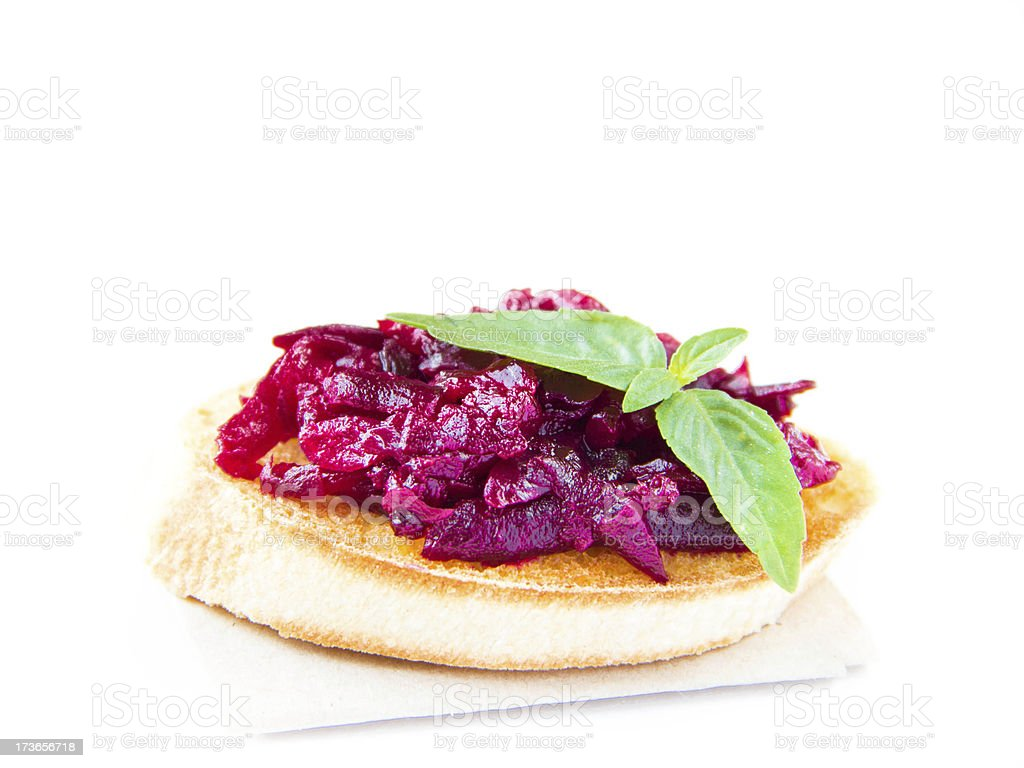 Classic Italian snack bruschetta with baked beet and fresh basil royalty-free stock photo
