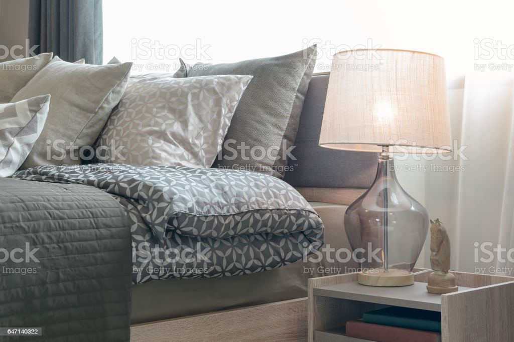 classic lamp style with alarm clock on table side in cozy bedroom stock photo