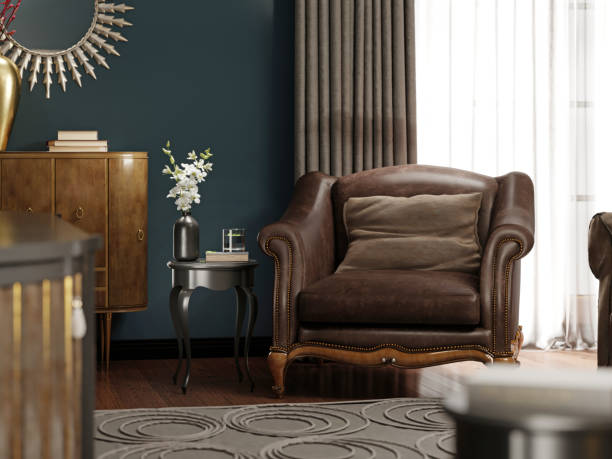 A classic leather armchair with a brown pillow, near the golden chest of drawers with decor, by the window.