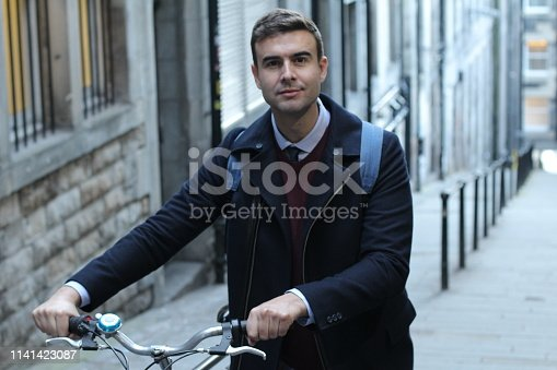 Classic looking man carrying bicycle upstairs.