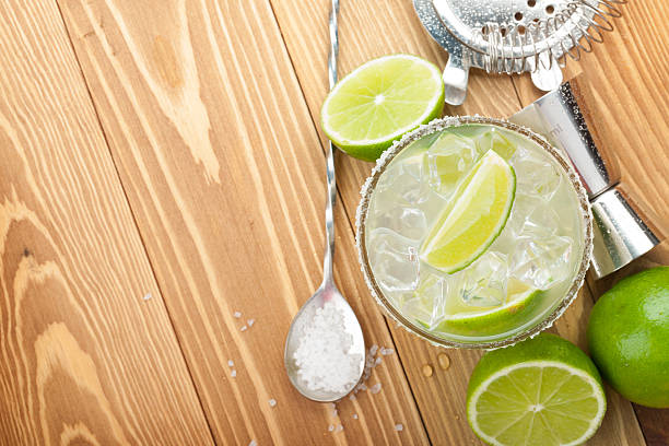 classic margarita cocktail with salty rim on wooden table - margarita drink stock photos and pictures