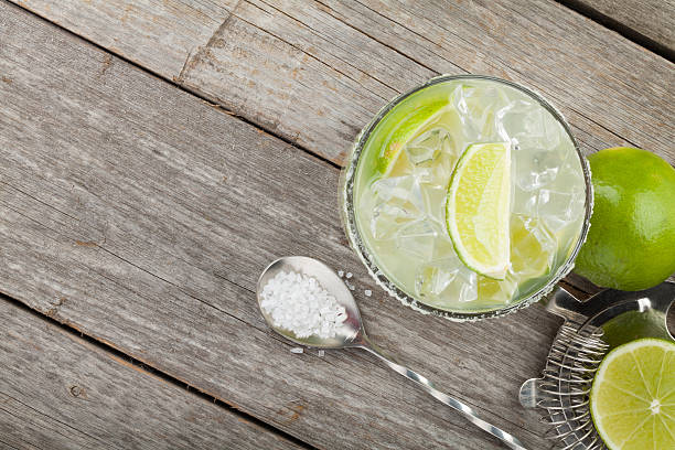 Classic margarita cocktail with salty rim Classic margarita cocktail with salty rim on wooden table with limes and drink utensils margarita stock pictures, royalty-free photos & images