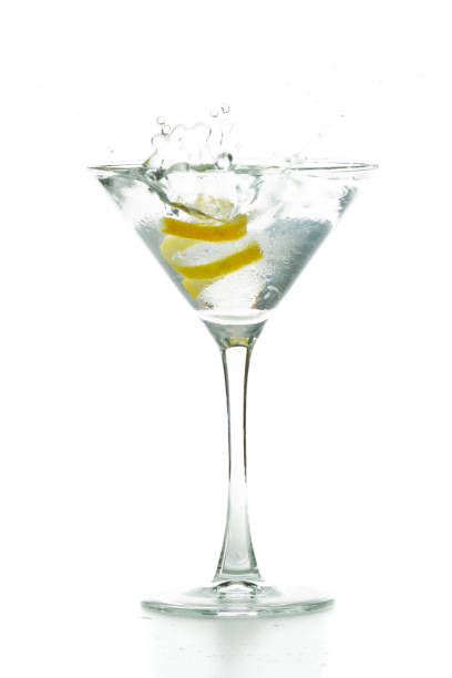 classic martini lemon twist falling in to a full martini glass isolated on a white background martini glass stock pictures, royalty-free photos & images