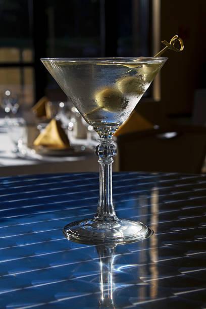 klassischer martini mit restaurant hintergrund - oliven wohnzimmer stock-fotos und bilder