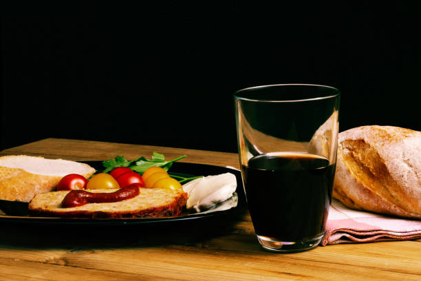 Classic meatloaf, cherry tomatoes, mozzarella, parsley, white bread in a black plate on a wooden background. Glass of pomegranate juice stock photo
