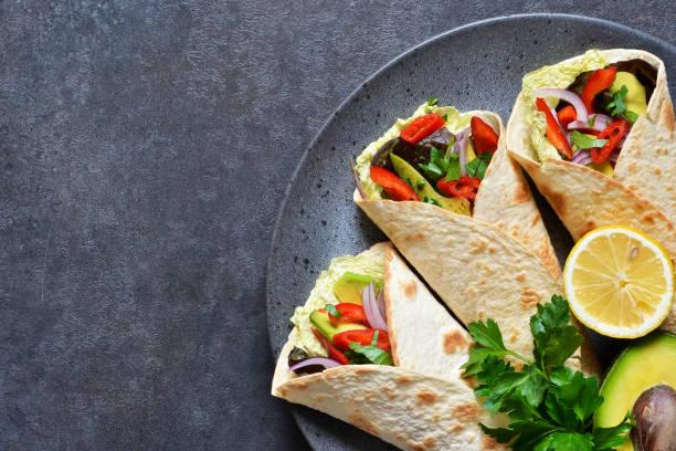 klassische mexikanische küche. tacos mit rindfleisch, avocado, chili und tomaten. ansicht von oben. - veggie wraps stock-fotos und bilder