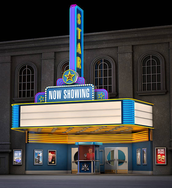 Classic Movie Theatre Exterior night shot of a retro illuminated neon movie theatre theater marquee commercial sign stock pictures, royalty-free photos & images