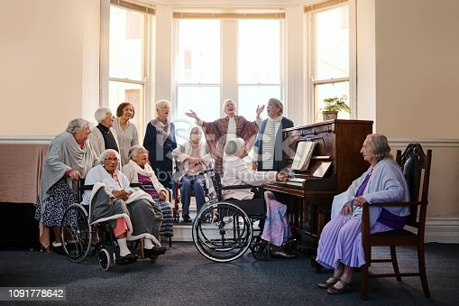 Shot of a group of senior women singing together and playing the piano at a retirement home