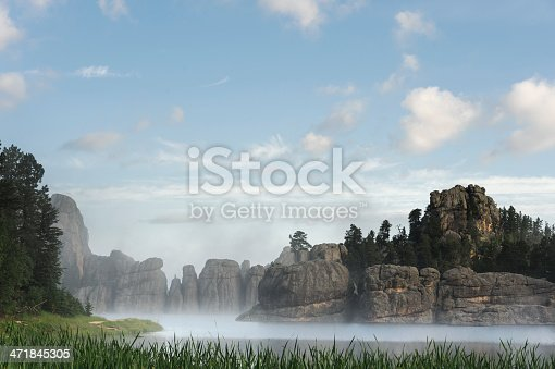 Remnants of fog on Sylvan Lake, surrounded by granite needles of rock topped by beautiful morning sky. Custer State Park in South Dakota, USA.