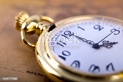 1030708556 istock photo Classic Necklace gold pocket watch on retro map 1045177536