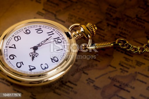 1030708556 istock photo Classic Necklace gold pocket watch on retro map 1045177574