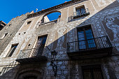 Classic old building with drawings of women in its facade in Bisbe street of Barcelona, Catalonia, Spain