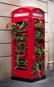 iconic old red public pay telephone being reused as a large vertical flower box, in the downtown district of Bath, England