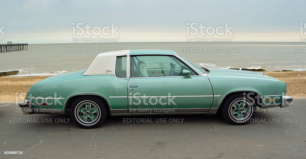 Classic Oldsmobile Cutlass Motor Car  parked on seafront promenade. stock photo