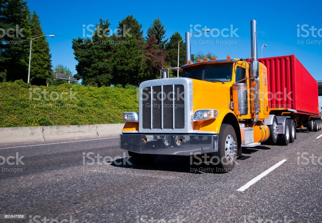 Classic orange big rig semi truck with red container on flat bed trailer running on the road stock photo