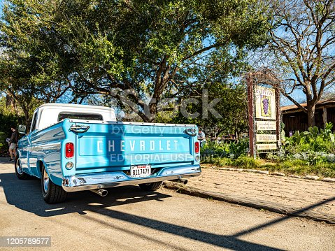 Gruene, Texas, USA- February 2, 20202. Center of a small town og Gruene in suburbs of San Antonio, Texas. Originally established by German emigrants, now a vibrant community of many different nationalities and backgrounds. Baby blue vintage Chevrolet pick up truck parked on the side of the road, near main town intersection. Restaurant venue in the background.