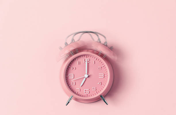 Classic pink alarm clock ringing at seven o'clock against pastel pink background