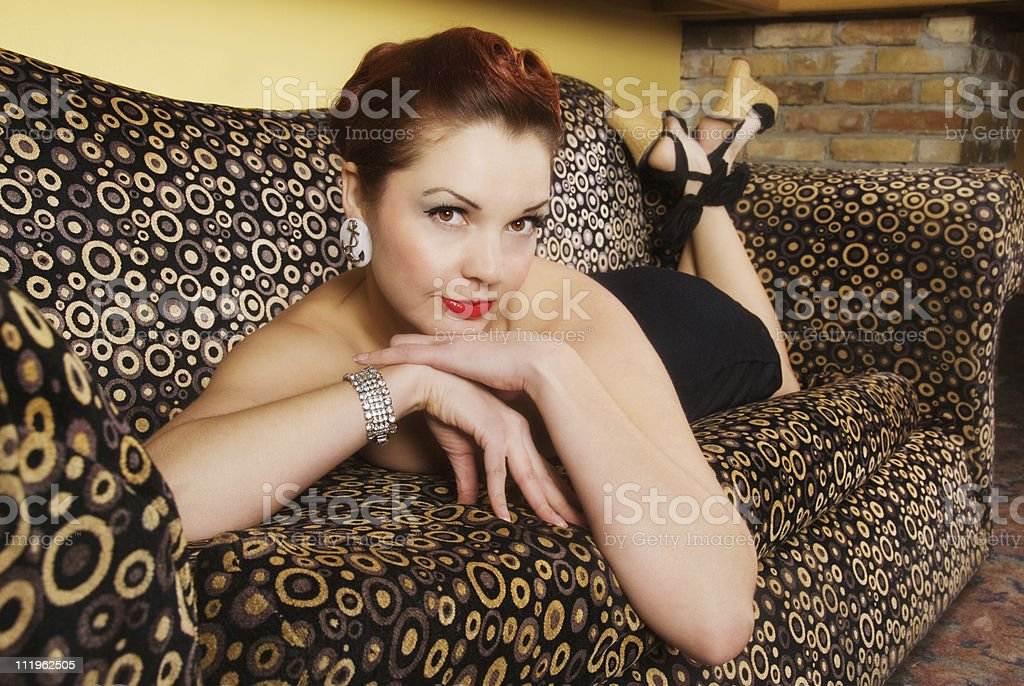 Classic Pinup: Beautiful sexy woman laying seductivly on a couch stock photo