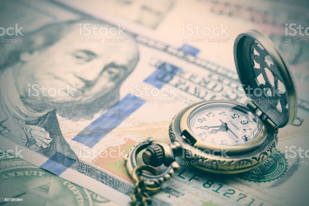 Classic pocket watch on a hundred US dollar bill. stock photo