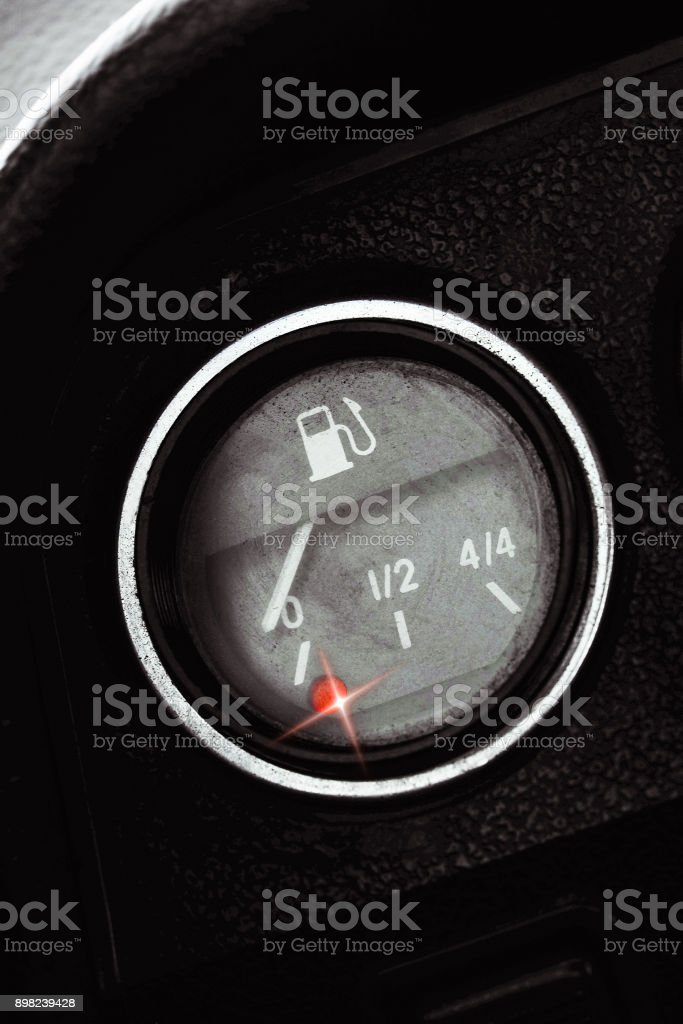 Classic pointer indicator of fuel level of the car. Low gasoline level with red alarm light lamp. Empty fuel tank. stock photo