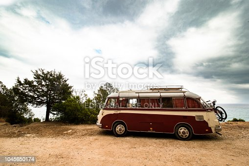 CALA GONONE - SARDINIA - ITALY - JULY 01, 2014: Classic Red and white Volkswagen camper parked on seafront promenade