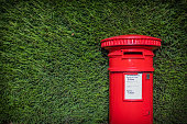 A Striking Red British Post Box Set Against A Neat Green hedgerow In England