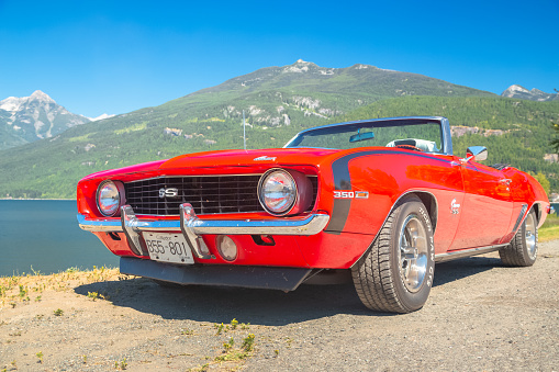 A vintage classic red 1969 Chevrolet Camaro SS 350 convertible car parked by Kootenay Lake in Kaslo, BC, Canada on a summer day.