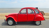 istock Classic Red Citroen 2CV  deux chevaux parked on seafront promenade. 1290515738