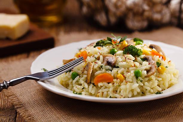 Clásico Risotto con champiñones y verduras servidos sobre una base de color blanco - foto de stock
