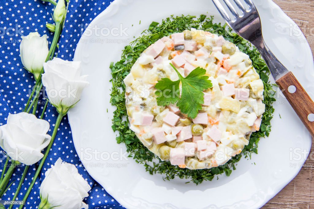 Classic Russian salad with sausage, peas, potatoes, carrots and mayonnaise, tasty traditional dish royalty-free stock photo