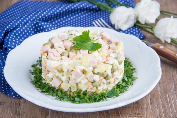 snack-klassiker russischer salat mit wurst, erbsen, kartoffeln, karotten und mayonnaise, schmackhafte traditionsgericht - schnelles weihnachtsessen stock-fotos und bilder