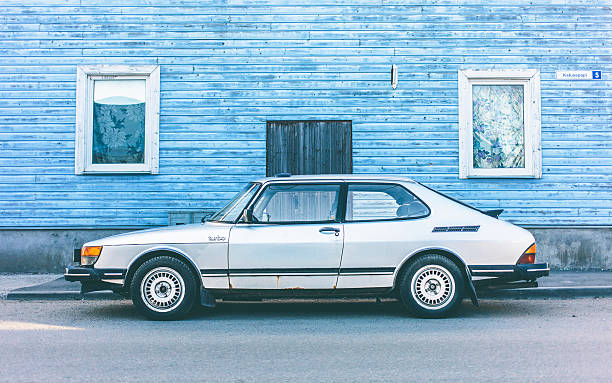Classic Saab. Tallinn, Estonia - May 1, 2013: Early 80s classic Saab 900 Turbo parked on town street in front of blue wooden house. saab stock pictures, royalty-free photos & images