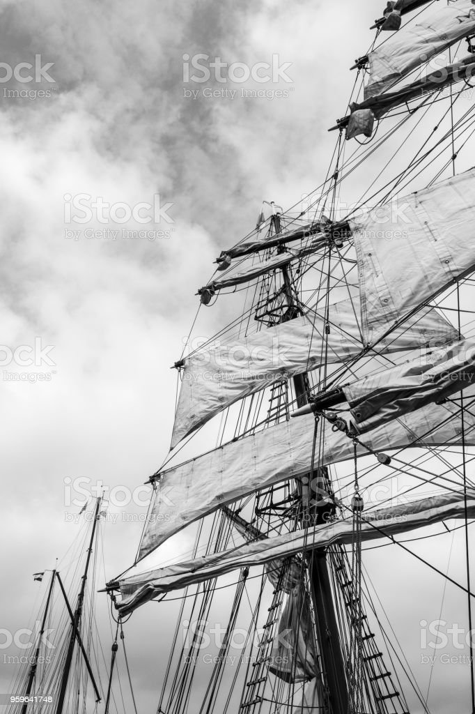 Classic sailing ship mast with sails with clouds in the background on...