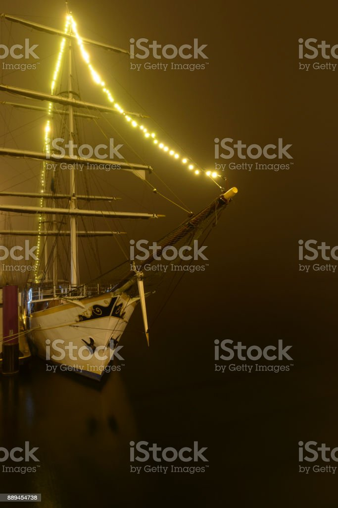 Classic sailing ship moored at the quay in Kampen during a foggy night stock photo