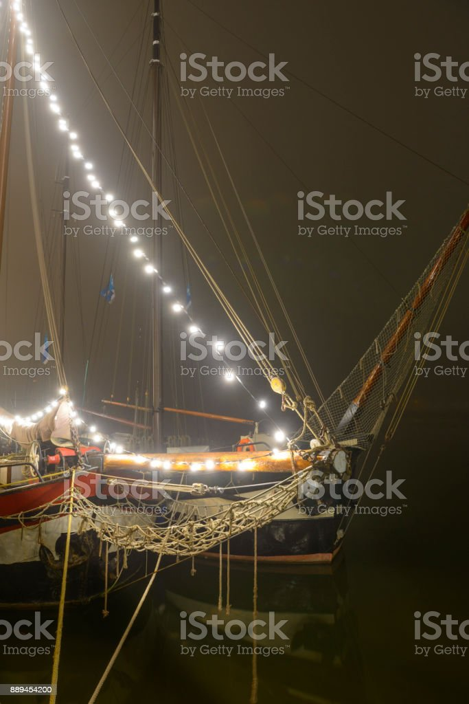 Classic sailing ships moored at the quay in Kampen during a foggy night stock photo