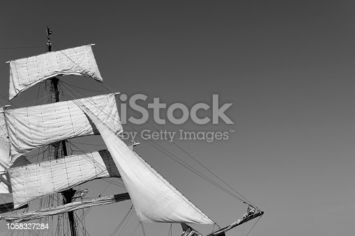 501889762istockphoto Classic sailing tall ship mast with sails in black and white 1058327284