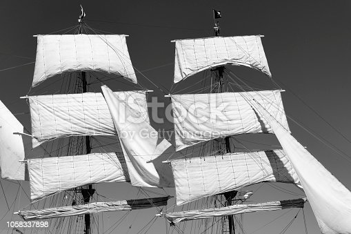 501889762istockphoto Classic sailing tall ship mast with sails in black and white 1058337898