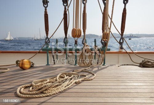 Rope coiled on the teak decking on a classic sailing yacht, with rigging, and view to other yachts in the background. Depth of field with focal point on foreground. Please see my other deck photos...