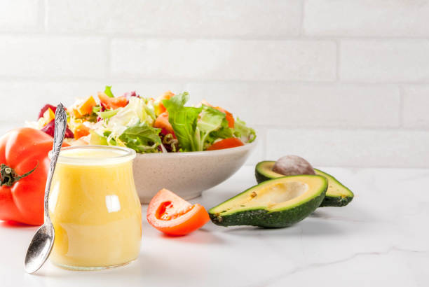 Classic salad dressings Classic honey mustard salad dressing, with fresh vegetables on white marble table, copy space vinaigrette dressing stock pictures, royalty-free photos & images