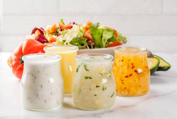 Classic salad dressings Set of classic salad dressings - honey mustard, ranch, vinaigrette, lemon & olive oil,  on white marble table, copy space vinaigrette dressing stock pictures, royalty-free photos & images