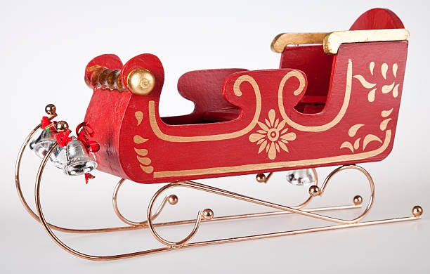 "Classic Santa Sleigh ""Classic Wooden toy Santa Sleigh, with gold trimmings, and silvers bells. Shot on white background side view."" sled stock pictures, royalty-free photos & images"