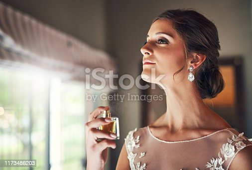 Shot of a beautiful young bride spraying perfume on her neck in preparation for her wedding day