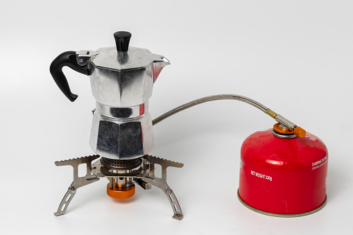 Classic silver moka pot, hand brews coffee maker on portable stove with red camping butane bottle, isolated on white background.