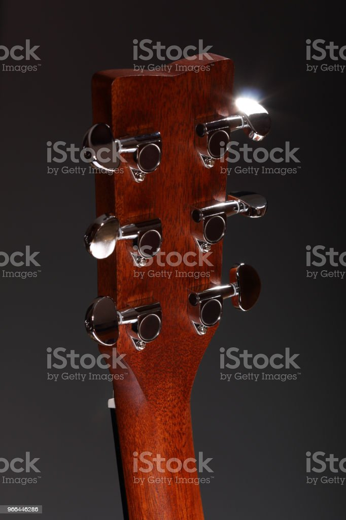 Classic six-stringed wooden acoustic guitar head stock photo
