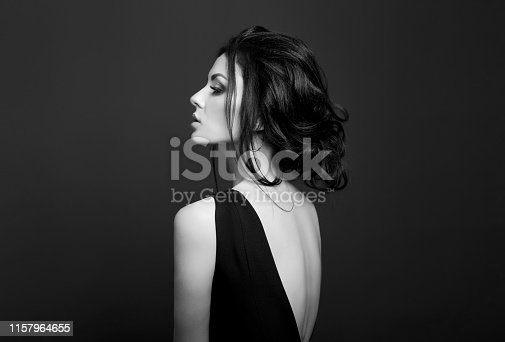 istock Classic Smokey makeup on woman face, beautiful big eyes. Fashion Perfect makeup, expressive eyes on girl face, smooth black eyebrows, licked brunette hair. Portrait of a woman on a dark background 1157964655