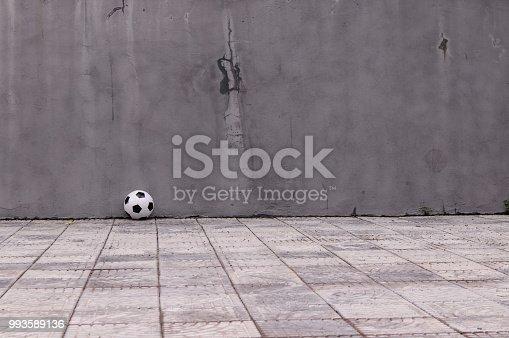 611897876istockphoto classic soccer ball near the gray wall 993589136