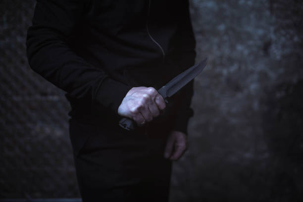 classic street villain holding up a knife - knife wound stock photos and pictures