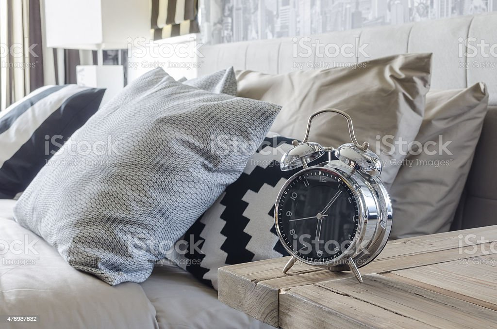 classic style alarm clock on wooden table in bedroom stock photo