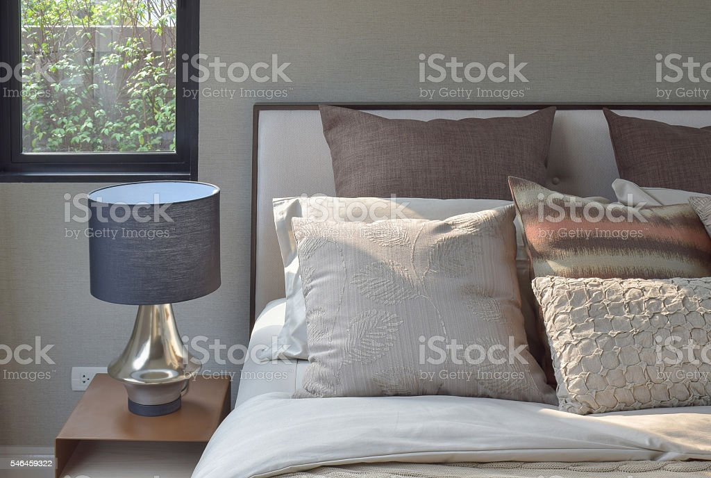classic style bedding and reading lamp on bedside table stock photo